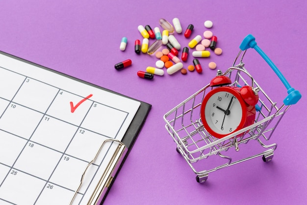 Carrinho de brinquedo com relógio e pílulas ao lado na mesa