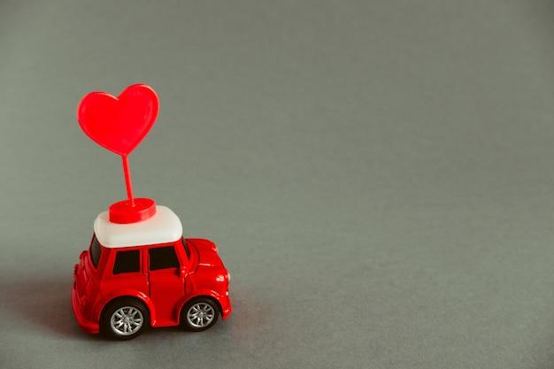 Carrinho de brinquedo vermelho carrega um coração vermelho