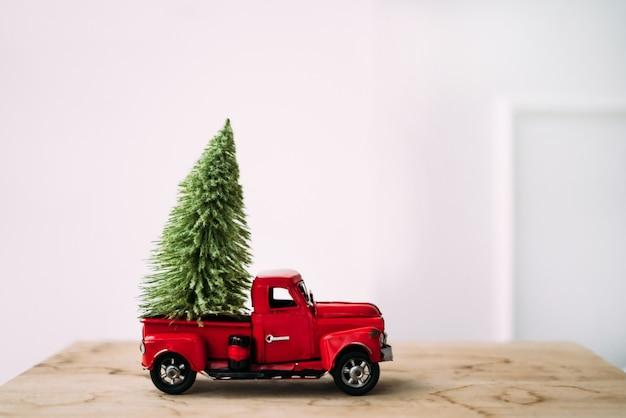 Carrinho de brinquedo vermelho com árvore de natal verde em pé de fundo branco e de madeira perto da parede.