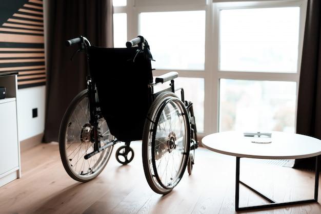 Carrinho de cadeira de rodas vazio moderno perto da janela na sala.