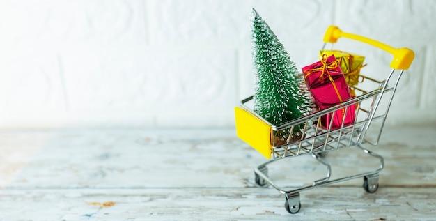 Carrinho de carrinho de loja de conceito de temporada de compras de natal cheio de caixa de presente em fundo de tijolo