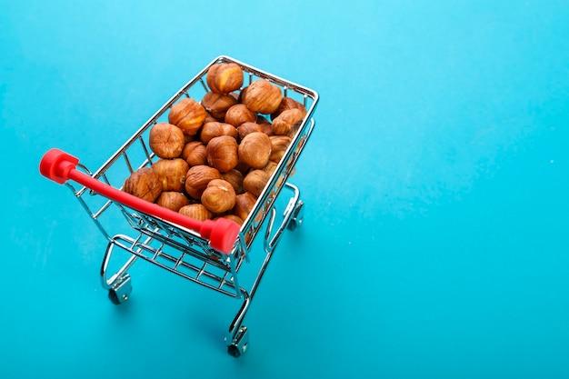Carrinho de comida cheio de avelãs descascadas em uma superfície azul