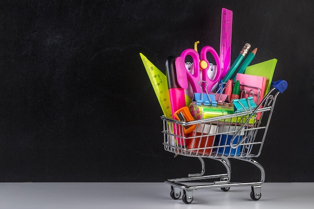 Carrinho de compras abastecido com material escolar e um quadro-negro