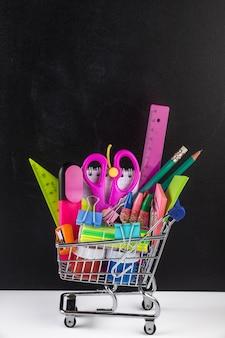 Carrinho de compras abastecido com material escolar e um quadro negro