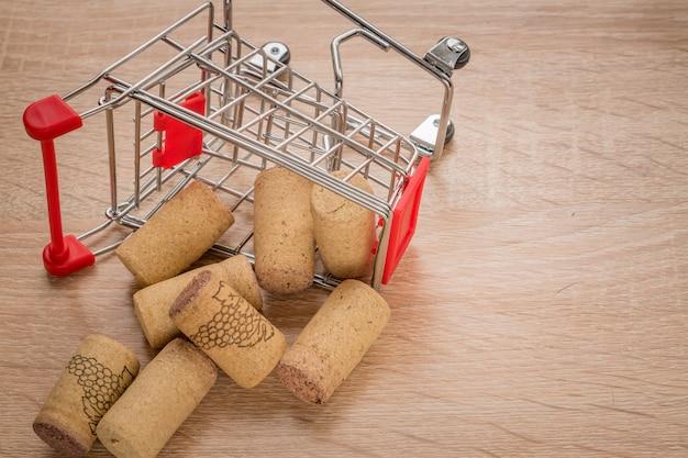Carrinho de compras caído cheio de rolhas de videira usadas, conceito em madeira