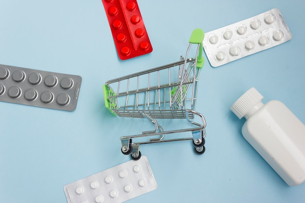 Carrinho de compras carregado com comprimidos em fundo azul. o conceito de medicamento e a venda e distribuição de medicamentos. copie o espaço.