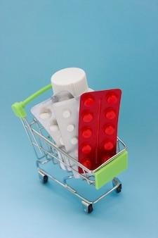 Carrinho de compras carregado com comprimidos em fundo azul