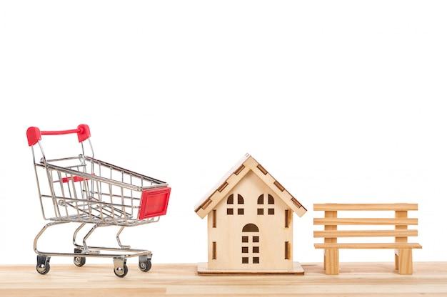 Carrinho de compras carrinho com pequena casa de madeira e bancada em uma mesa