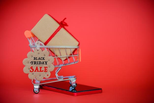 Carrinho de compras, celular e caixa de presente com cartão de venda de sexta-feira negra