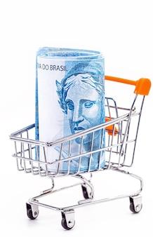 Carrinho de compras, cesta de compras, com nota de 100 reais do brasil dentro.