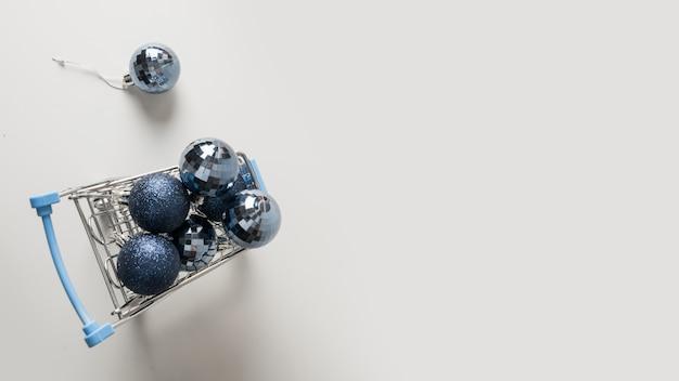 Carrinho de compras cheio de bolas azuis.