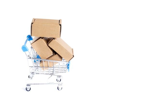Carrinho de compras cheio de caixas de papelão, isolado no fundo branco.