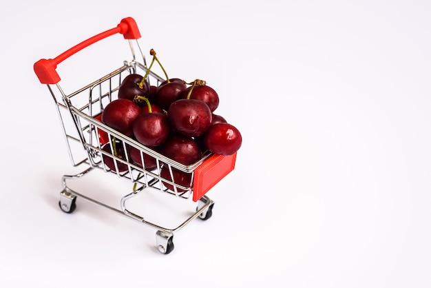 Carrinho de compras cheio de cerejas maduras, saudáveis e nutritivas compras