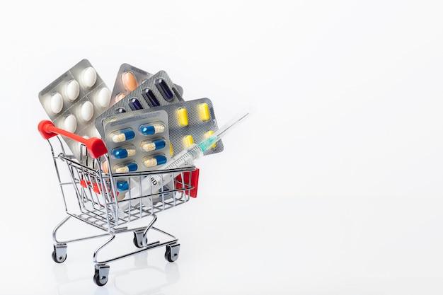 Carrinho de compras cheio de comprimidos, cápsulas e seringa plástica em fundo branco. prescrição de medicamentos para tratamento medicamentoso. medicamento farmacêutico. tema de farmácia.