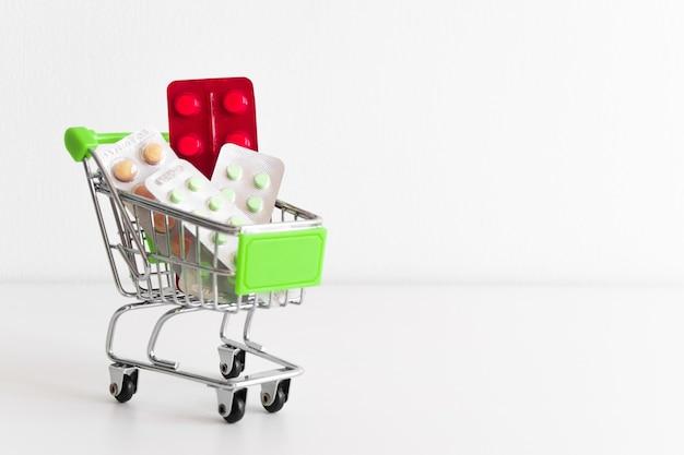 Carrinho de compras cheio de comprimidos e medicamentos em fundo branco. carrinho de loja em miniatura com espaço para seu texto. banner simulado da farmácia copyspace