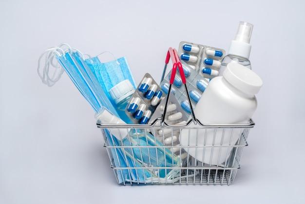 Carrinho de compras cheio de comprimidos e suprimentos médicos sobre fundo cinza claro