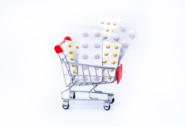 Carrinho de compras cheio de comprimidos em fundo branco isolado