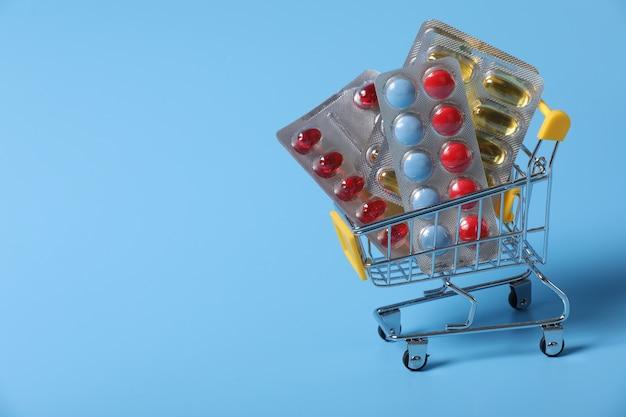 Carrinho de compras cheio de comprimidos. fundo azul
