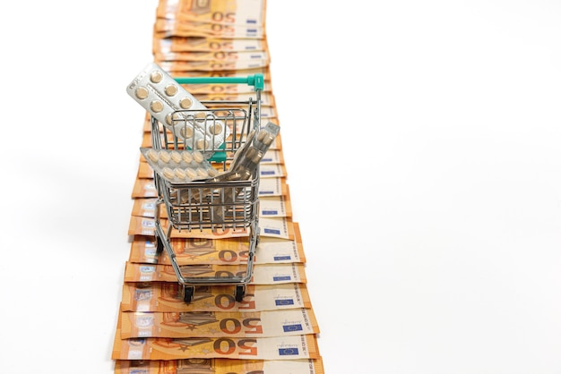 Carrinho de compras cheio de comprimidos na estrada de notas de cinquenta euros, isolado no branco, copie o espaço