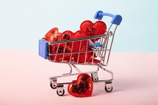 Carrinho de compras cheio de corações vermelhos brilhantes. conceito do dia de são valentim