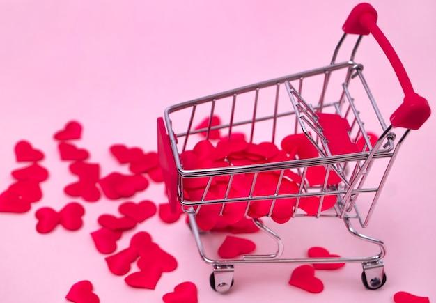 Carrinho de compras cheio de corações vermelhos em uma cesta decorativa de fundo rosa com pequenos corações