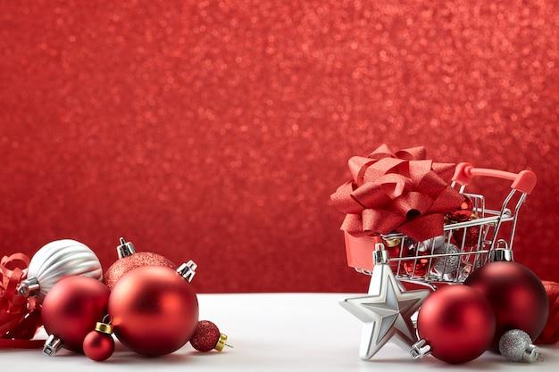 Carrinho de compras cheio de enfeites de natal em fundo vermelho