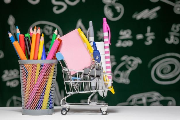 Carrinho de compras cheio de material escolar