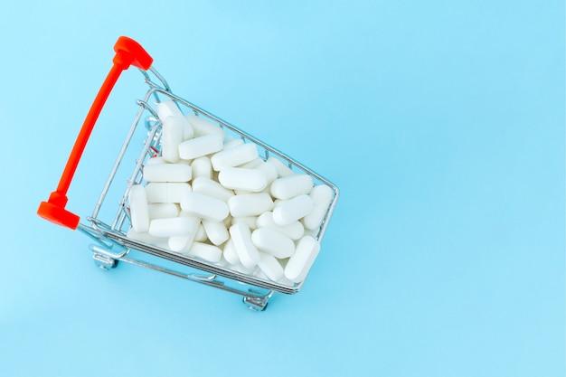 Carrinho de compras cheio de medicamento, isolado no fundo azul