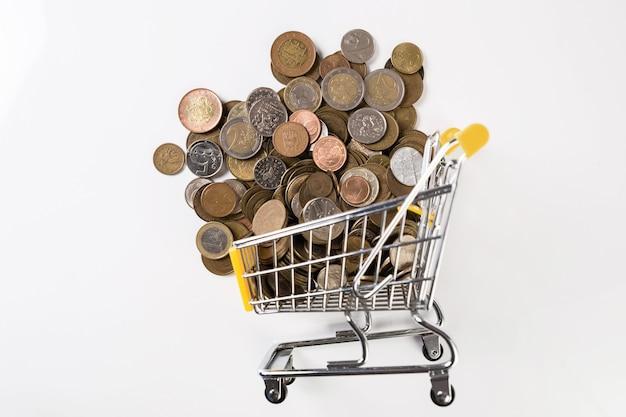 Carrinho de compras cheio de moedas na superfície branca