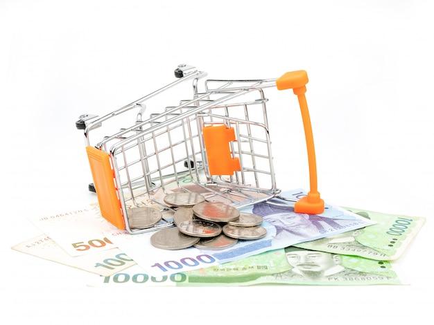 Carrinho de compras cheio de notas e moedas, isoladas no fundo branco. conceito de compras.