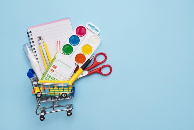 Carrinho de compras cheio de papelaria escolar na mesa azul