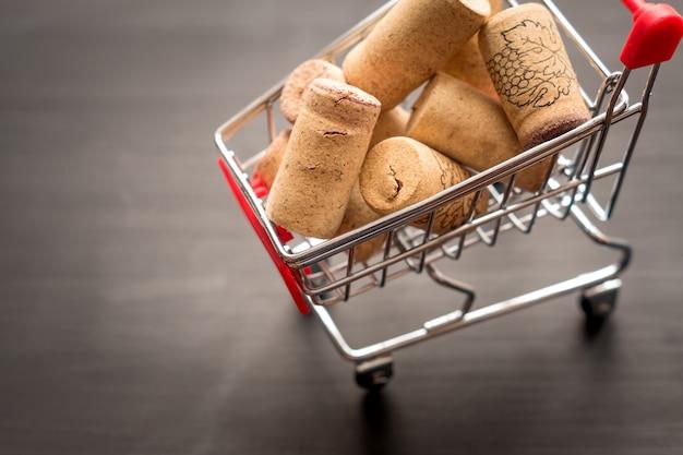 Carrinho de compras cheio de rolhas de videira usadas, conceito em preto de madeira