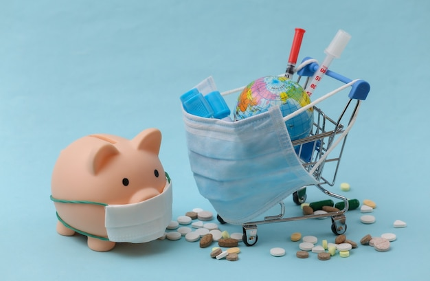 Carrinho de compras, cofrinho em máscara médica com tubos de ensaio, seringas, pílulas e um globo sobre um fundo azul. saúde global