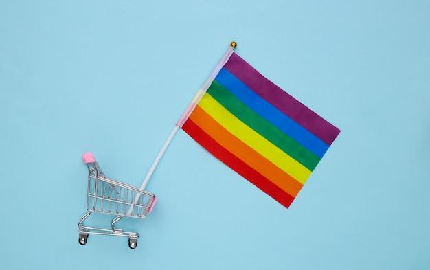 Carrinho de compras com a bandeira do arco-íris lgbt sobre fundo azul. parada gay, liberdade, tolerância