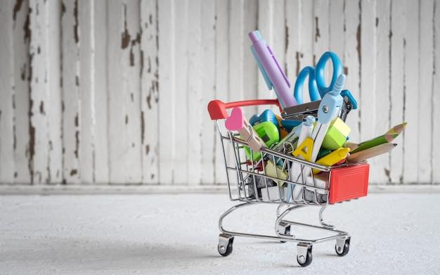 Carrinho de compras com artigos de papelaria e material escolar