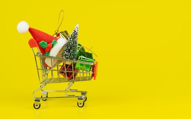 Carrinho de compras com árvore de natal e caixas de presente em miniatura em fundo amarelo