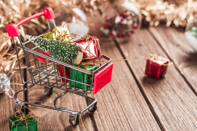 Carrinho de compras com árvore de natal e caixas de presente em miniatura