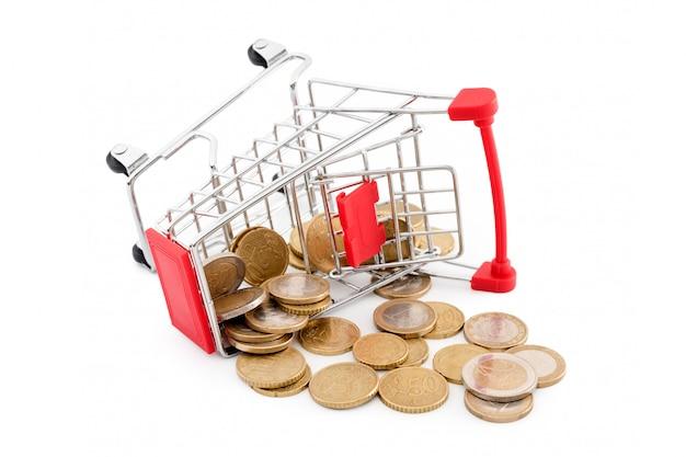 Carrinho de compras com as moedas de euro nele está caindo no fundo branco. representação conceitual de um fracasso, pobreza e falência. tema de compras, venda e dinheiro de volta no supermercado. copyspace para texto.