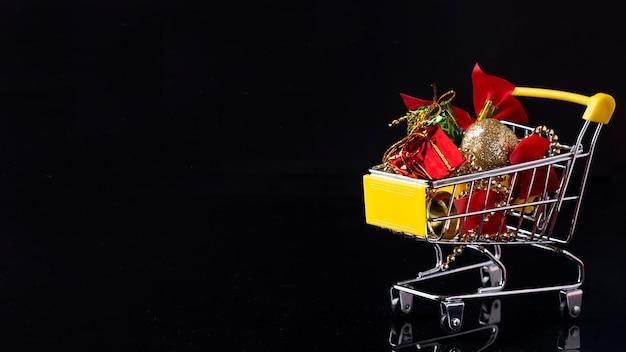 Carrinho de compras com brinquedos de natal em um preto. compras online de natal. copie o espaço