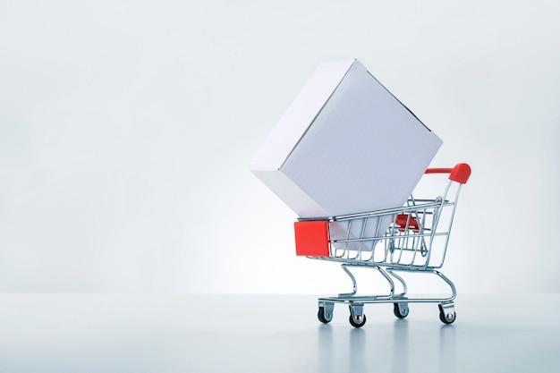 Carrinho de compras com caixa de pacote em fundo cinza branco com espaço de cópia. conceito de entrega.