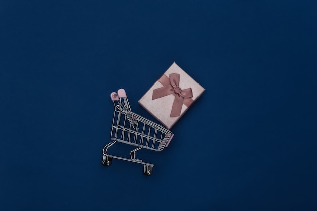Carrinho de compras com caixa de presente em fundo azul clássico. cor 2020. vista superior.