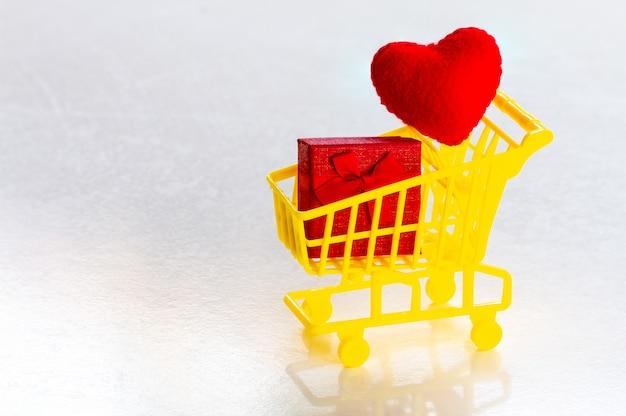 Carrinho de compras com caixa de presente vermelha e corações vermelhos de confete em um espaço de cópia de fundo cinza