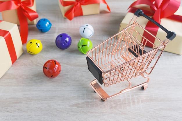 Carrinho de compras com caixa de presentes de natal fita vermelha e sino colorido em madeira