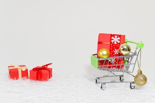 Carrinho de compras com caixas de presente e esferas douradas em um floco de neve em um fundo branco