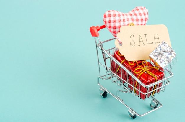 Carrinho de compras com caixas de presente e etiqueta de venda em superfície brilhante