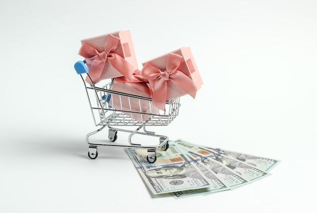 Carrinho de compras com caixas de presente e notas de cem dólares em um fundo branco.