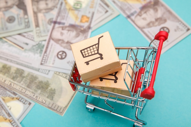 Carrinho de compras com caixas e notas de dólar em azul