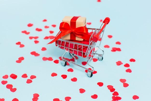 Carrinho de compras com caixinha de presente com fita vermelha em fundo azul com muitos corações