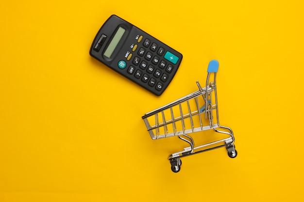 Carrinho de compras com calculadora em um amarelo. cálculo econômico de compras, custos de compra.