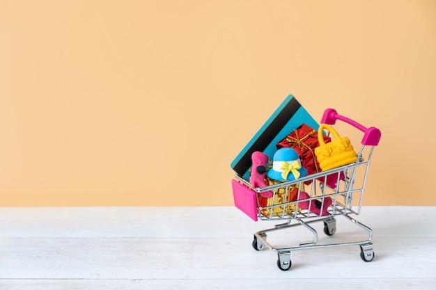 Carrinho de compras com cartão de crédito e acessórios de mulher com espaço de cópia
